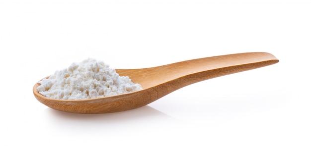 Pilha de farinha de trigo branca na colher de pau branco