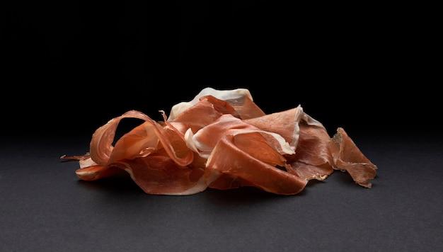 Pilha de fatias de jamon, presunto de porco cru na superfície preta