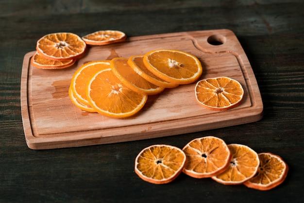 Pilha de fatias de laranjas frescas e secas em uma tábua retangular de madeira em uma mesa escura que pode ser usada como parede