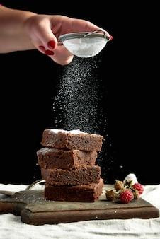 Pilha de fatias quadradas de bolo de chocolate brownie polvilhadas com açúcar branco