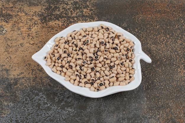 Pilha de feijão branco seco no prato em forma de folha.