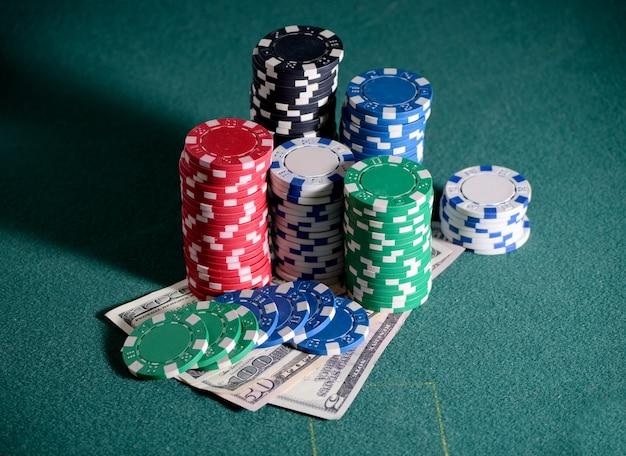 Pilha de fichas de cassino e notas de dólar na mesa de pôquer