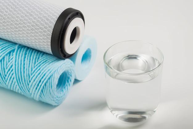 Pilha de filtros de água e copo d'água