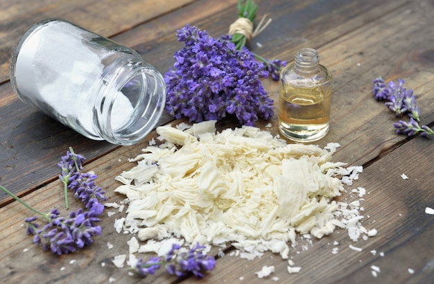 Pilha de flocos de sabão com óleo essencial e ramo de flores de lavanda e bicarbonato de sódio em fundo de madeira