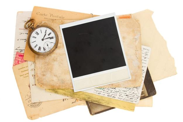 Pilha de fotos antigas com relógio antigo isolado no fundo branco