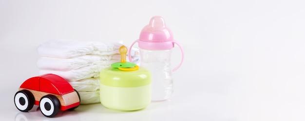 Pilha de fraldas descartáveis para bebês, um brinquedo de carro e mamadeiras em fundo branco