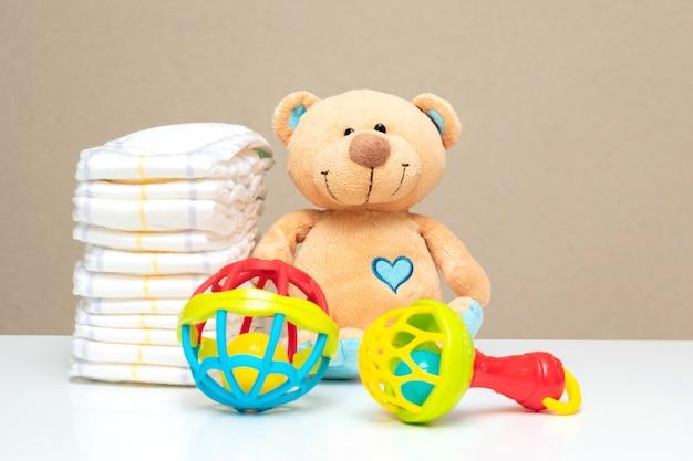 Pilha de fraldas, fofo urso de pelúcia com brinquedos na mesa para chá de bebê com espaço de cópia.