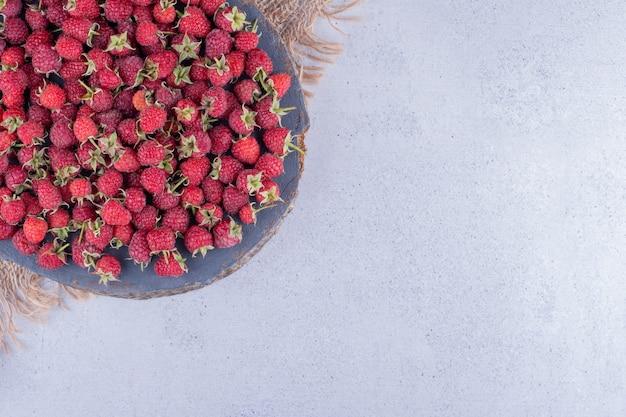 Pilha de framboesas em uma placa de madeira com fundo de mármore. foto de alta qualidade