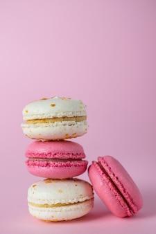 Pilha de franceses deliciosos macarons rosa e brancos de sabores diferentes
