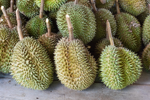 Pilha de frutas durian sentar na mesa de madeira no mercado.