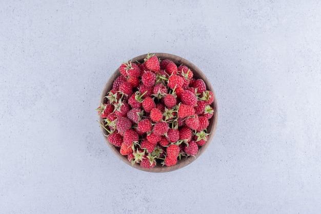 Pilha de frutas em uma tigela de madeira com fundo de mármore.