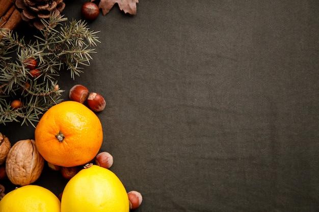Pilha de frutas frescas, cones e nozes no tecido verde escuro. plano de ação de graças com copyspace