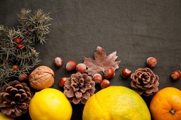 Pilha de frutas frescas, cones e nozes no tecido verde escuro