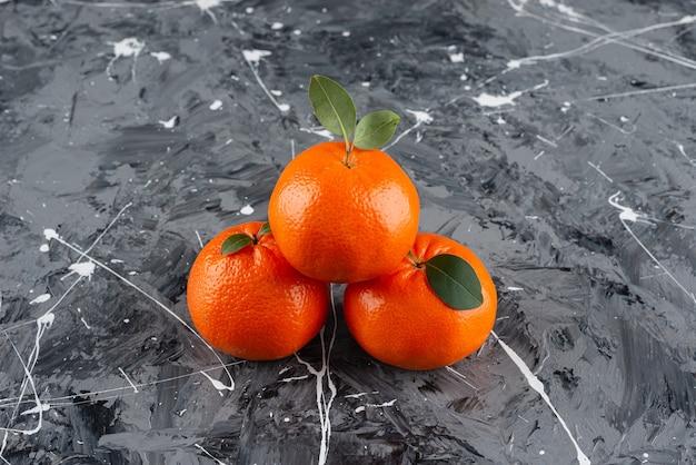 Pilha de frutas frescas de tangerina com folhas colocadas sobre uma mesa de mármore.