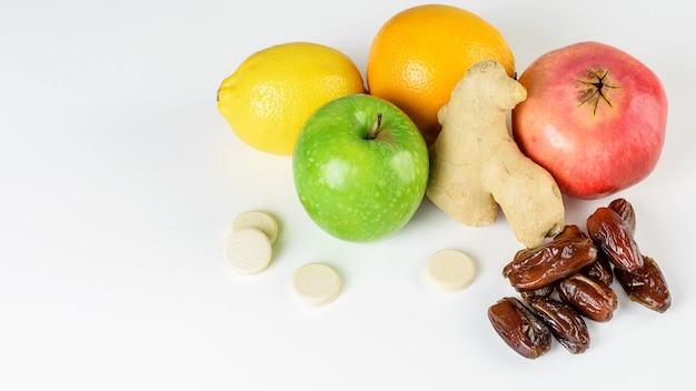 Pilha de frutas (maçã verde, limon, laranja, granada), gengibre, tâmaras e multivitaminas para estimulação da imunidade e defesa contra vírus