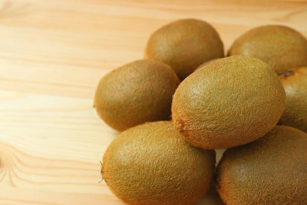 Pilha de frutos de kiwi maduros frescos na mesa de madeira