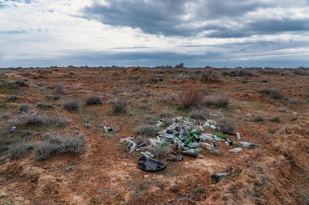 Pilha de garrafas de vidro em campo, poluição ambiental
