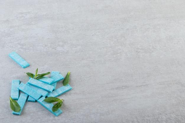 Pilha de gomas azuis com folhas de hortelã em fundo cinza.