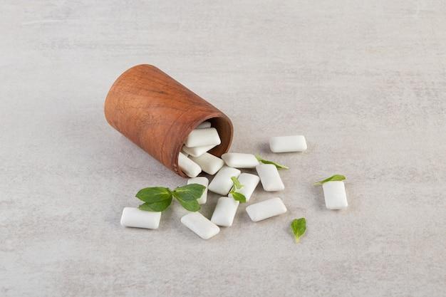 Pilha de gomas brancas com folhas de hortelã.