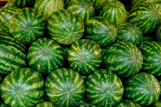 Pilha de grandes melancias verdes maduras no supermercado que podem ser usadas