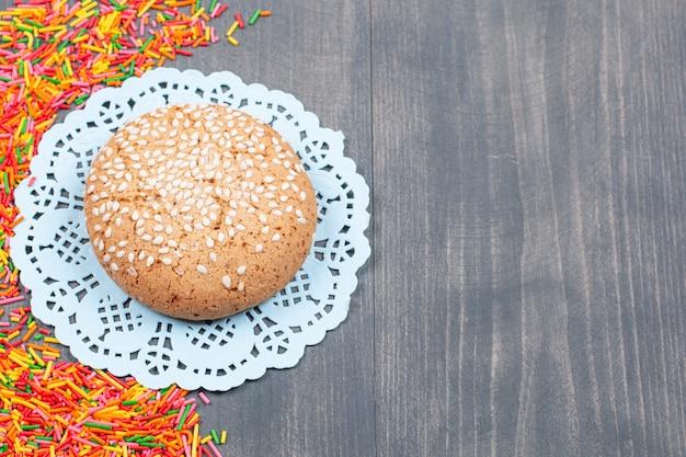 Pilha de granulado colorido ao redor de um biscoito saboroso