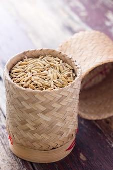 Pilha de grãos de arroz não moídos na cesta de bambu
