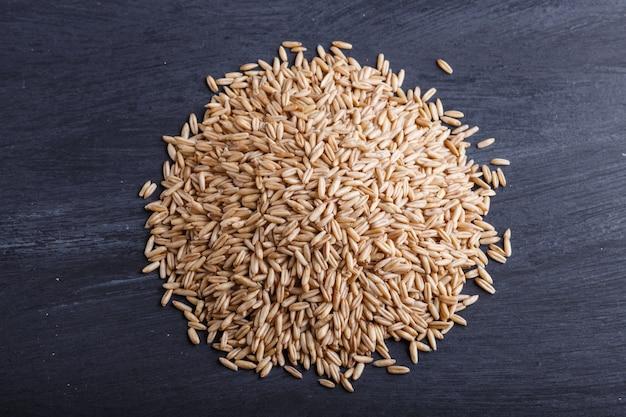 Pilha de grãos de aveia isolado no preto