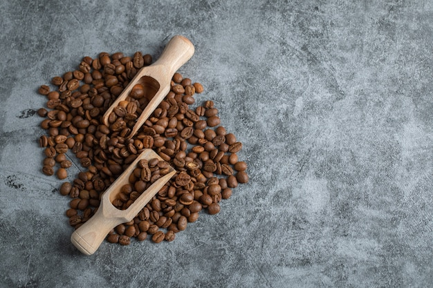 Pilha de grãos de café aromáticos e colheres de madeira em fundo de mármore