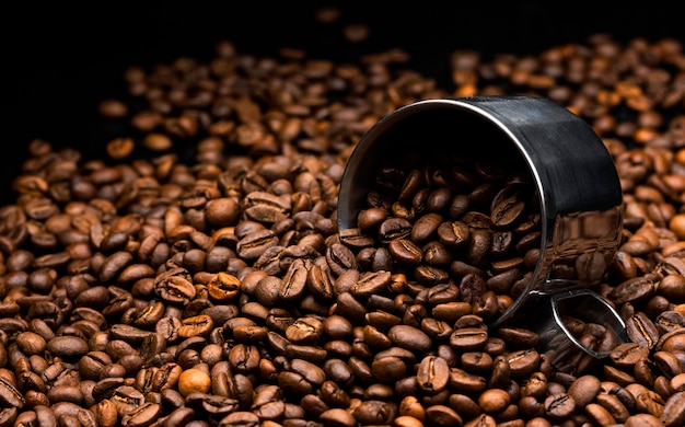 Pilha de grãos de café com copo de metal, close-up, fundo escuro