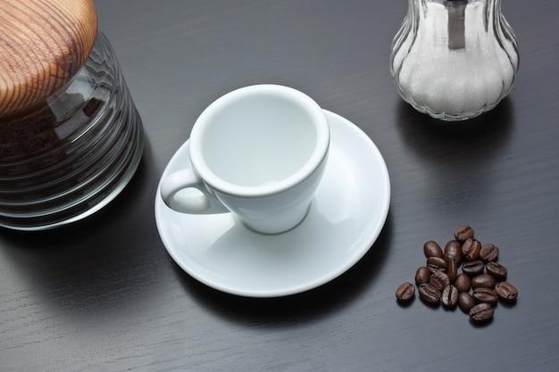 Pilha de grãos de café e uma xícara em uma mesa cinza
