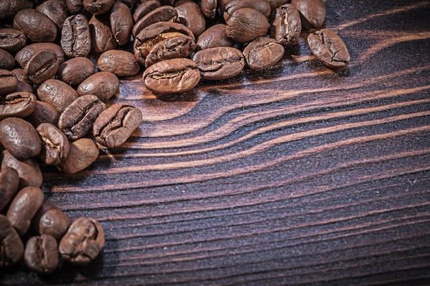 Pilha de grãos de café em uma placa de madeira vintage