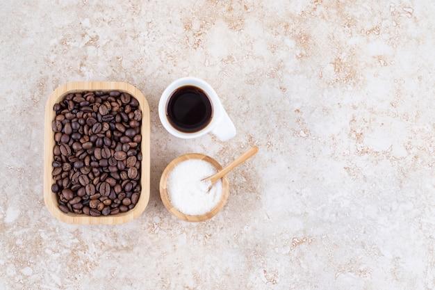 Pilha de grãos de café em uma travessa de madeira ao lado de uma pequena tigela de açúcar e uma xícara de café