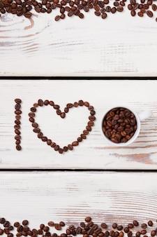 Pilha de grãos de café em uma xícara branca. eu amo o conceito de café. mesa de madeira branca em backgorund.