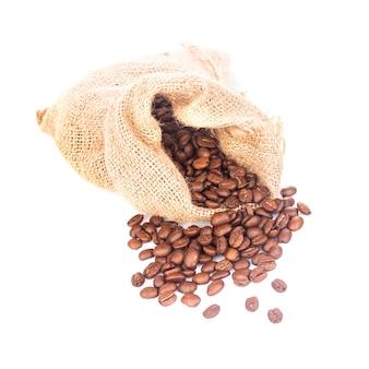 Pilha de grãos de café no saco isolado no branco