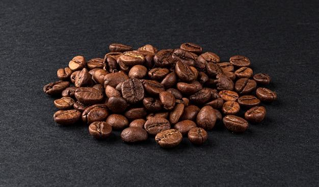 Pilha de grãos de café torrados em fundo preto