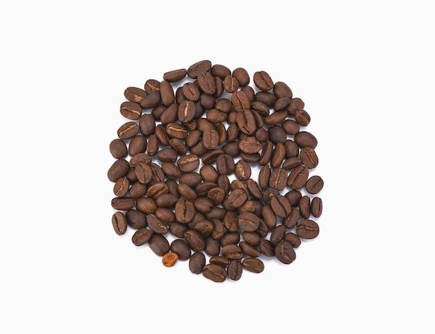 Pilha de grãos de café torrados isolada no branco. vista de cima