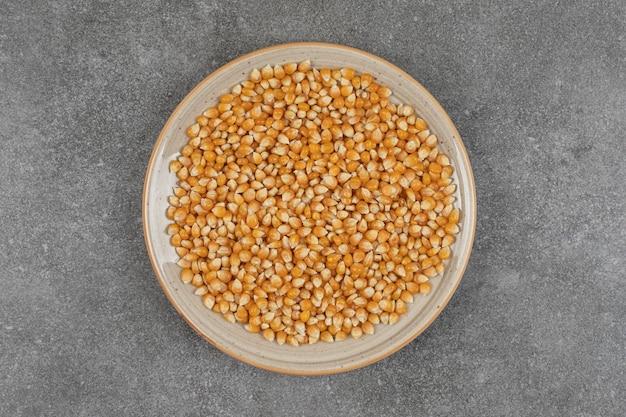 Pilha de grãos de milho crus na placa de cerâmica.