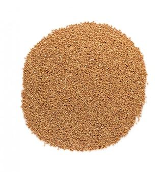 Pilha de grãos de trigo mourisco crus secos isolados na vista superior de fundo branco. kasha russa ou trigo pseudocereal cru cortado