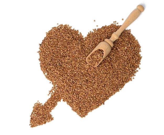 Pilha de grãos de trigo sarraceno cru, vista superior. sêmolas dispostas em forma de coração e isoladas