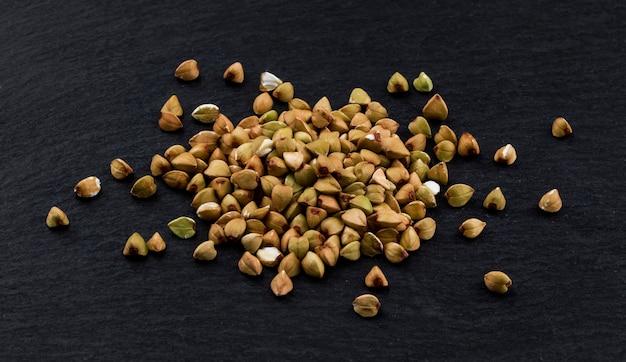 Pilha de grãos de trigo sarraceno verde sobre fundo preto