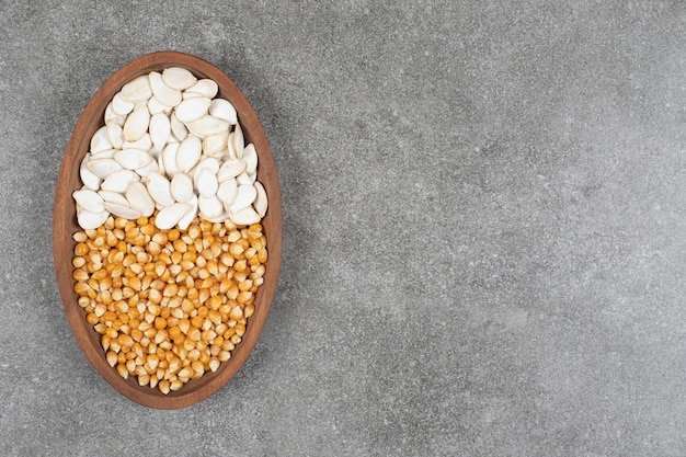 Pilha de grãos secos e sementes de abóbora na placa de madeira.