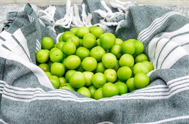 Pilha de greengages na toalha de cozinha e no grunge, vista lateral.