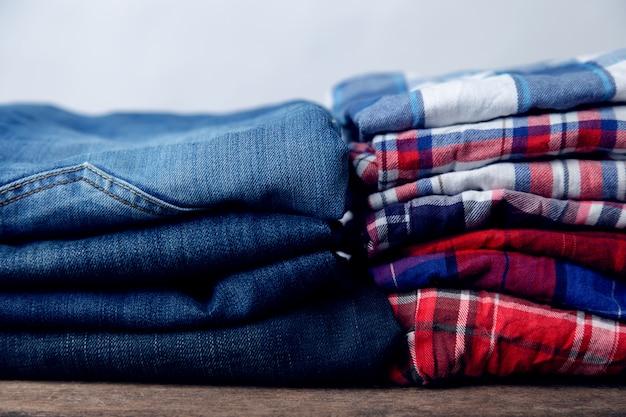 Pilha de jeans e camisas quadriculada