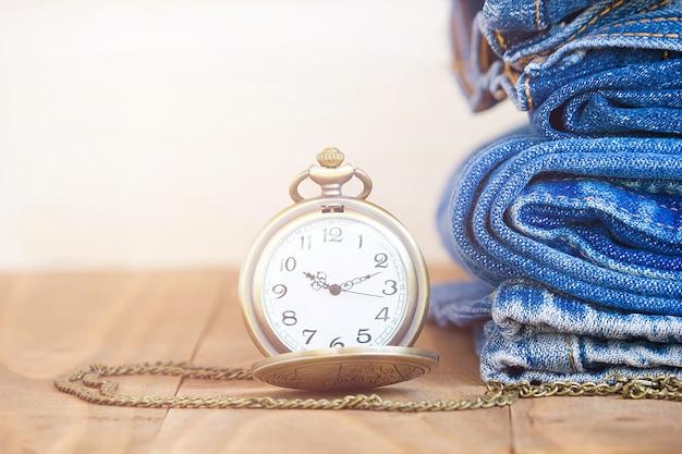 Pilha de jeans e relógios clássicos no velho de madeira