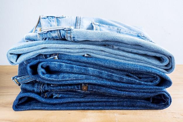 Pilha de jeans na mesa de madeira.