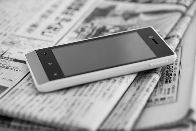 Pilha de jornais com smartphone nele