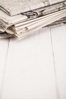 Pilha de jornais sobre uma mesa branca