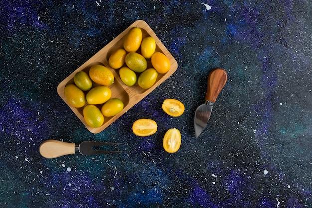 Pilha de kumquats em uma placa de madeira cortada inteira ou pela metade