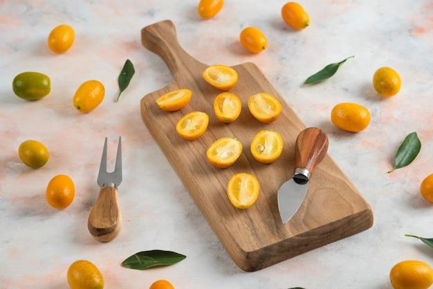 Pilha de kumquats, inteiros ou meio cortados em uma tábua de madeira