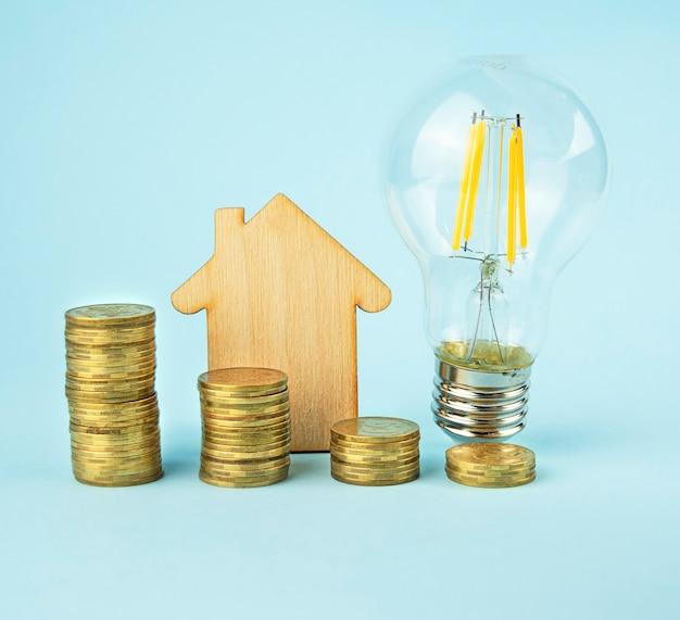 Pilha de lâmpadas, casa de madeira e moedas em fundo azul claro